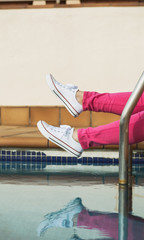 Woman with canvas shoes and pink jeans, in a pool area.