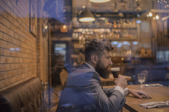 Businessman with long beard drink in cigar club. serious bar customer sit in cafe drinking ale. Date meeting of hipster awaiting in pub. Beer time. Bearded man rest in restaurant with beer glass.