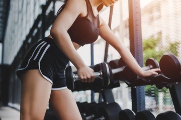 Fitness woman in training. Woman lifting dumbbell