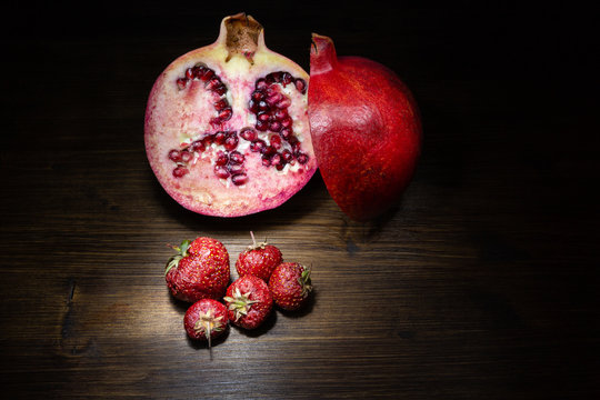 Pomegranate and strawberries, positioned on an old table and illuminated using light painting technique.