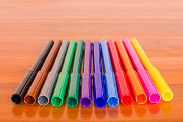 Row of twelve color pens on brown wood background