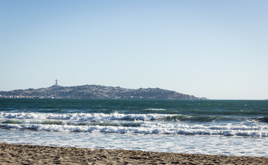 Views of Coquimbo city and the famous Cruz del Tercer Milenio from empty beach in La Serena, Chile