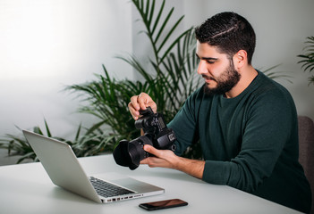 Young photographer working with his camera in the studio. Business concept