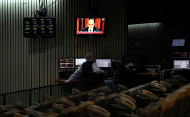 A man works on the floor of Buenos Aires Stock Exchange as an image of former Argentine Economy Minister Cavallo is broadcasted on a tv screen in Buenos Aires