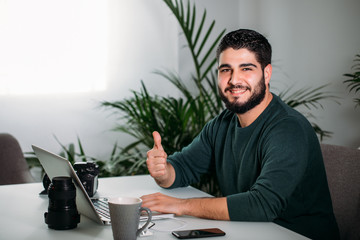 Young man working with his studio and showing thumbs up. Business concept