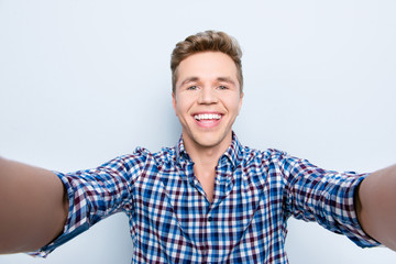 Close up portrait of cheerful surprised astonished glad excited carefree handsome guy with toothy beaming smile taking selfie on mobile smartphone isolated on gray background holding with two hands