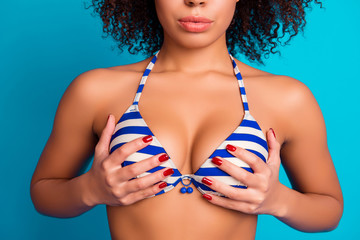 Cropped close up photo of charming tempting sexual afro-american woman's breast dressed in striped swim bra, isolated on bright blue background