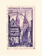 An old french postage stamp with an image of a church and old houses