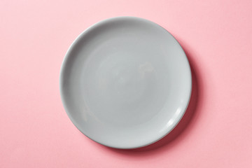 Grey plate on pink background, from above