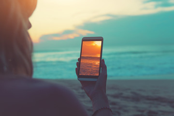 Girl looking at the photo on smartphone while enjoying the ocean / sea sunset.