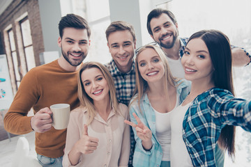 Self portrait of cheerful, joyful, positive students managers shooting selfie on front camera in modern office showing two fingers, like, peace, hi sign, holding cup with coffee, partnership