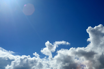 White clouds on blue sky with sun light and flare.