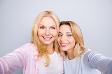Self portrait of pretty charming cute trendy stylish attractive women shooting selfie on front camera having beaming smiles casual outfits isolated on grey background