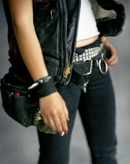 Young adult wearing studded belt and holding cigarette.