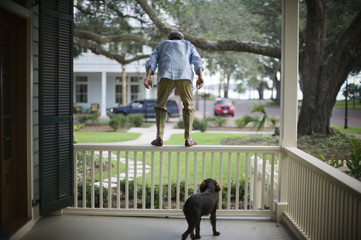 Mature man being watched by his dog while preparing to jump from a balcony railing.