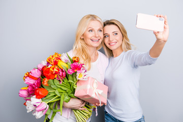 Cheerful joyful blogger having fun with mom using smart phone shooting self postrait on front camera video call enjoying event holding colorful tulips gift case in package isolated on grey background