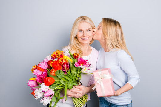 Lovely girl kissing in cheek her mom prepare gift case in pink package with white bow, holding big bouquet of colorful tulips in hands enjoying  rest relax leisure isolated on grey background