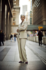 Portrait of a businesswoman standing on a city street and smiling.