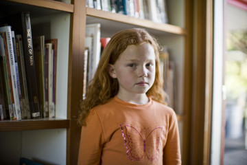 Portrait of a young girl standing in front of a bookcase inside her home.
