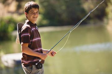Teenage boy having fun fishing on a lake.