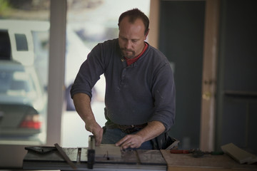 Male builder measuring a piece of wood on a work bench.