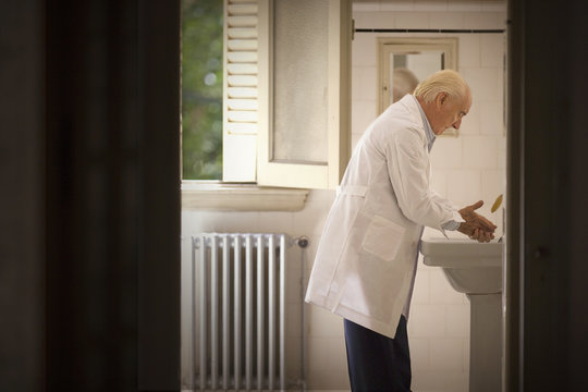 A senior man is washing his hands.