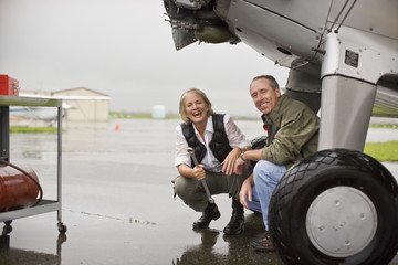 Portrait of happy man and woman crouching under an airplane while it rains