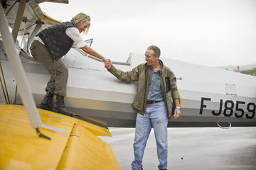 Man helping woman off wing of airplane