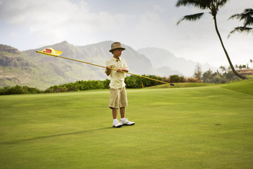 Young boy holds a golf flag.