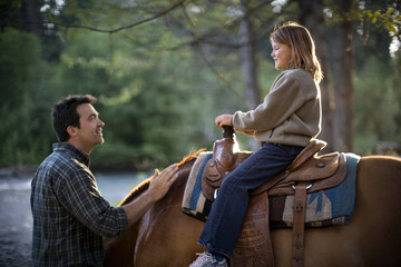 Mid-adult man talking to his teenage daughter atop a horse.
