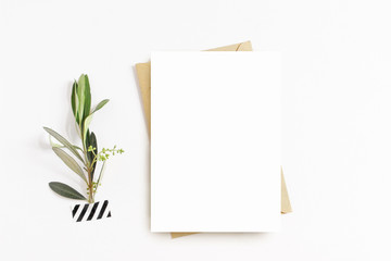 Feminine stationery, desktop mock-up scene. Blank greeting card, craft envelope, washi tape and with olive branch.White table background. Flat lay, top view. Wall mural