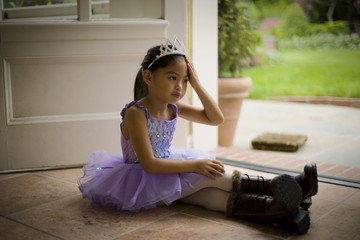 Sitting young girl wearing a tutu and tiara.
