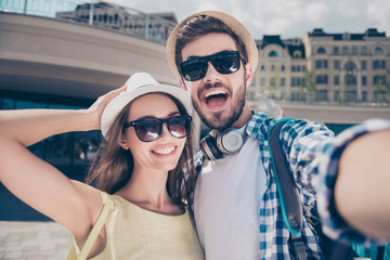 Positive trendy cheerful couple in caps having journey, trip, meeting outdoor shooting self portrait on front camera, sunny day sunshine, beautiful woman handsome man with bristle, casual outfit