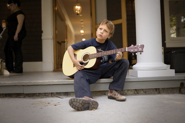 Boy playing an acoustic guitar while sitting on a porch step.