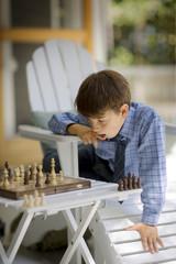 Boy sitting outside playing chess.
