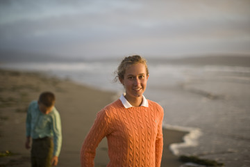 Portrait of a smiling teenage girl standing on the beach.