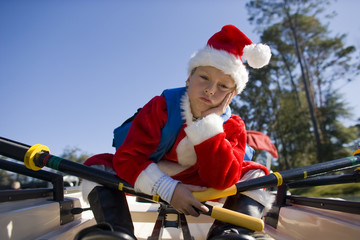 Boy wearing santa costume in rowboat