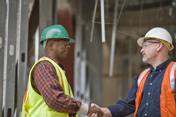 Two builders shaking hands on a construction site