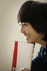Teenage girl smiling while holding a notebook.
