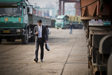 Businessman with briefcase using smartphone walking at construction site