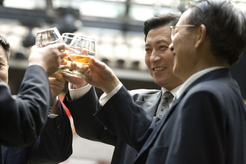 Mid-adult businessmen toasting a drink in a bar.
