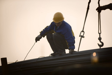 Young adult male construction worker atop steel poles attached to a crane on a wharf.