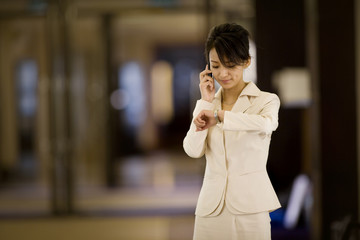 Young adult business woman checking her watch while using a cellphone in an office.
