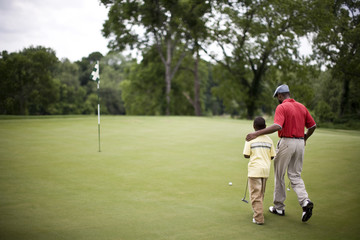 Father and son walking across a golf course