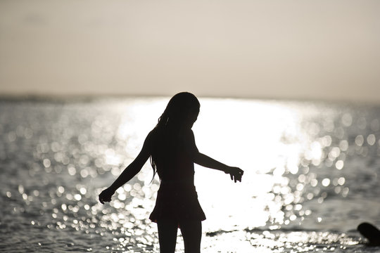 Silhouette of a girl standing in the shallows on a beach at sunset.