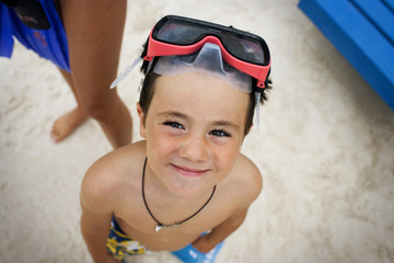 Portrait of a young boy wearing a pair of swimming goggles.