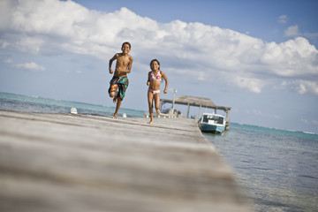 Smiling young girl and her older brother running along a wooden jetty in their swimwear.