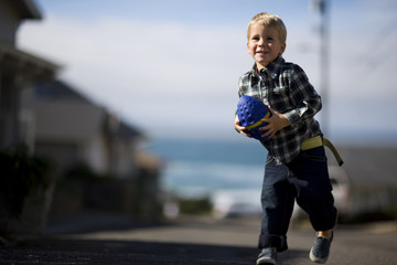 Portrait of a young boy playing outside with a toy football.