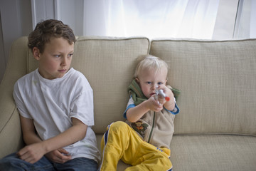 Young toddler aiming a toy gun while seated next to his older brother on a sofa in the living room.