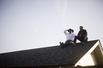 Men sitting on roof of house